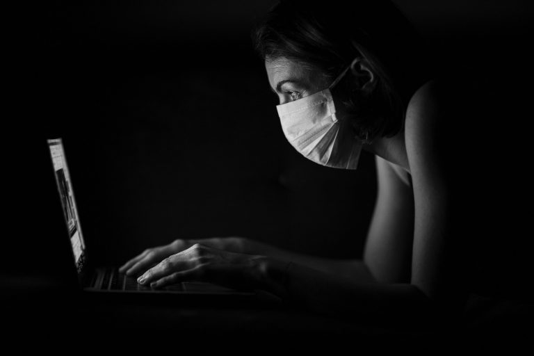 woman wearing a mask in from on the PC